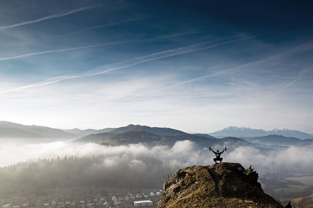 Bartlomiej Kolusz head coach of Percepcja Crossfit is making crossfit exercises on the top of the rock, on the second plan Tatra Mountains. Slovakia. (Photo by Adam Kokot/Caters News Agency)