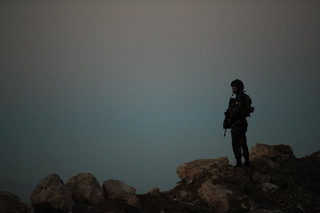 A Kurdish Peshmerga soldier is silhouetted while French President Francois Hollande visits a military outpost on the outskirts of the Islamic State-held city of Mosul, outside the Kurdish city of Irbil, Iraq, Monday, January 2, 2017. Hollande is in Iraq for a one-day visit. (Photo by Christophe Ena/AP Photo)