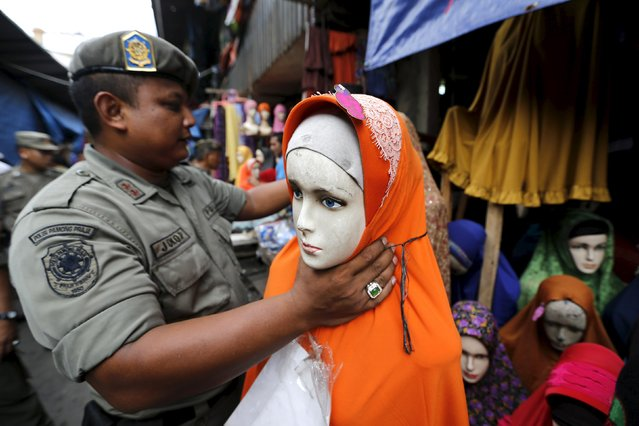 A Civil Service policeman moves a manequin belonging to a hijab vendor during a sweep operation against illegal steet vendors causing traffic congestion at Tanah Abang market in Jakarta, April 7, 2015. (Photo by Reuters/Beawiharta)
