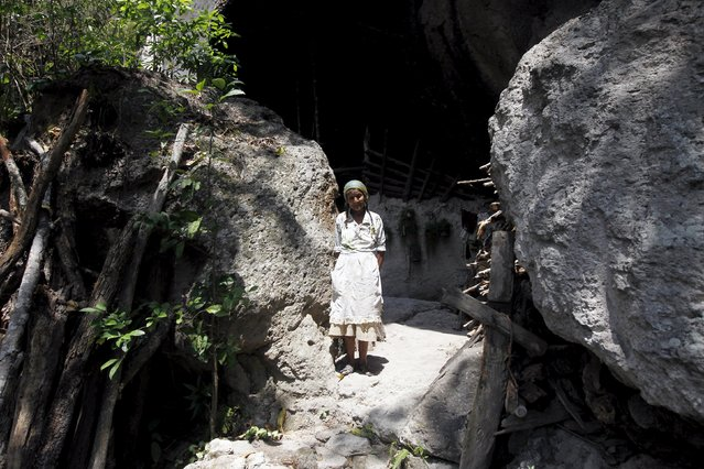 Francisca Gomez stands at an entrance to her home, a cave where she has been living for the past 50 years, in the mountains on the outskirts of Chusmuy April 21, 2015. (Photo by Jorge Cabrera/Reuters)