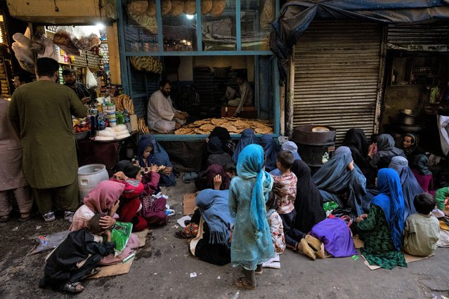 Afghan women and children sit in front of a bakery waiting for bread donations in Kabul's Old City, Afghanistan, Thursday, September 16, 2021. (Photo by Bernat Armangue/AP Photo)