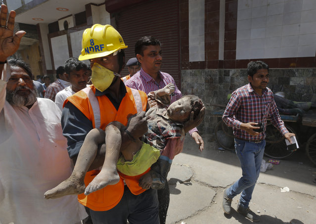 A members of National Disaster Response Force carries an injured child, found under the debris of a residential building, to an ambulance, in New Delhi, India, Wednesday, April 22, 2015. One man and a child were killed and at least nine others were injured when a three-story residential building collapsed following an explosion in a cooking gas cylinder, according to local news agency Press Trust of India. (Photo by Manish Swarup/AP Photo)
