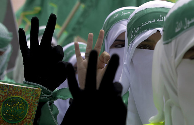 Palestinian students supporters of the Islamic militant movement of Hamas hold the Koran and show three fingers, their electoral number, as they march during the election campaign for students' council  at the Polytechnic University in the West Bank city of Hebron, 20 April 2015. (Photo by Abed Al Haslhamoun/AFP Photo)