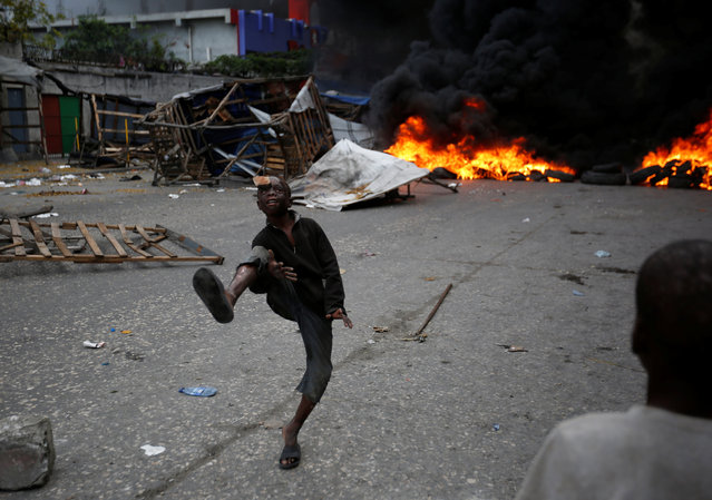A boy juggles in front of a burning barricade during a protest against the government in the streets of Port-au-Prince, Haiti, February 10, 2019. (Photo by Jeanty Junior Augustin/Reuters)