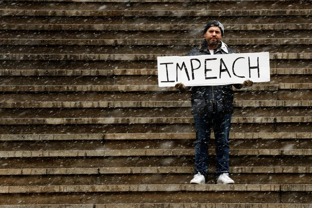 Ilan Bachrach holds a sign protesting the presidency of U.S. President Donald Trump on the steps of Federal Hall during a snow fall in New York, U.S., January 31, 2017. (Photo by Lucas Jackson/Reuters)