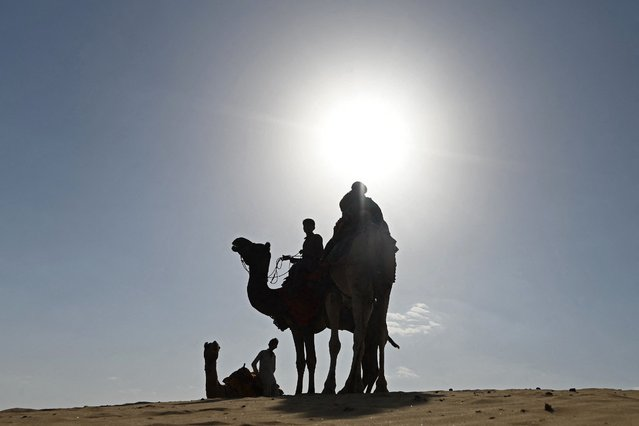Camel owners wait for tourists in the sand dunes of Thar Desert at Sam village in India's Rajasthan state on October 7, 2021. (Photo by Sajjad Hussain/AFP Photo)