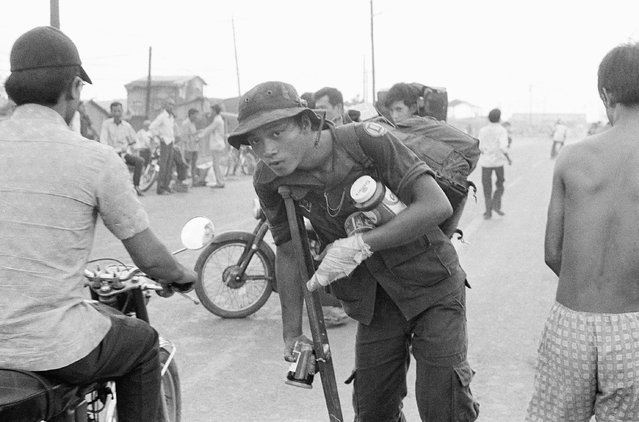 A crippled South Vietnamese war veteran limps away on crutch with food looted from abandoned U.S. installations after evacuation of Saigon, April 29, 1975. (Photo by AP Photo)