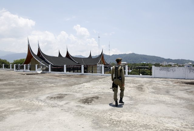 A civil service police officer walks on the roof of a building used as tsunami evacuation centre, a day after a 7.8 magnitude quake struck far out at sea near Padang, West Sumatra province, Indonesia March 3, 2016. (Photo by Darren Whiteside/Reuters)