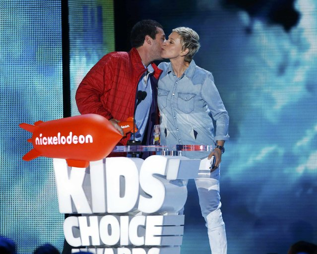 "Actor Adam Sandler accepts the award for Favorite Animated Movie for ""Hotel Transylvania 2"" from Ellen DeGeneres during Nickelodeon's 2016 Kids' Choice Awards in Inglewood, California March 12, 2016. (Photo by Mario Anzuoni/Reuters)"