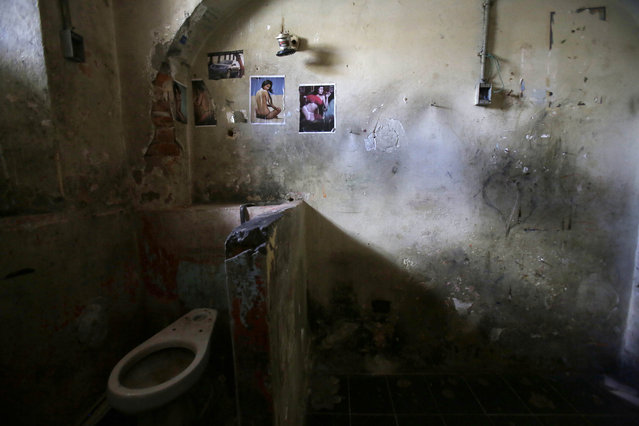 """This April 9, 2015 photo shows the bathroom area of a prison cell decorated with pin-up girls and a car at the now empty Garcia Moreno Prison, during a guided tour for the public in Quito, Ecuador. Psychologist Oscar Ortiz, who worked with the inmates behind these walls, says most people believe prison is the worst place, with the worst people. """"But I have now lived many years and I have concluded that the prison is simply a reflection of our society"""". (Photo by Dolores Ochoa/AP Photo)"""