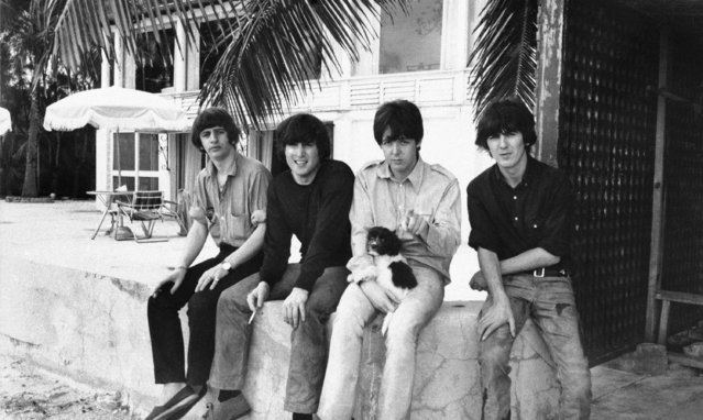 The Beatles sit on a stone fence in Nassau, Bahamas on February 22, 1965. From left to right are; Ringo Starr, John Lennon, Paul McCartney and George Harrison. (Photo by AP Photo)