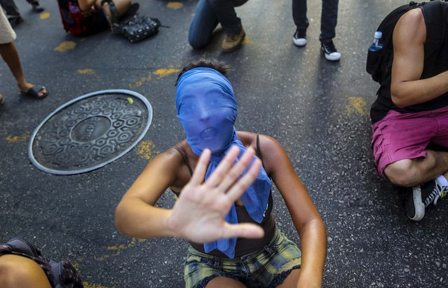 A masked girl shouts while sitting on the street, in protest against the increase on bus fares in Rio de Janeiro, Brazil, on February 10, 2014. (Photo by Leo Correa/Associated Press)