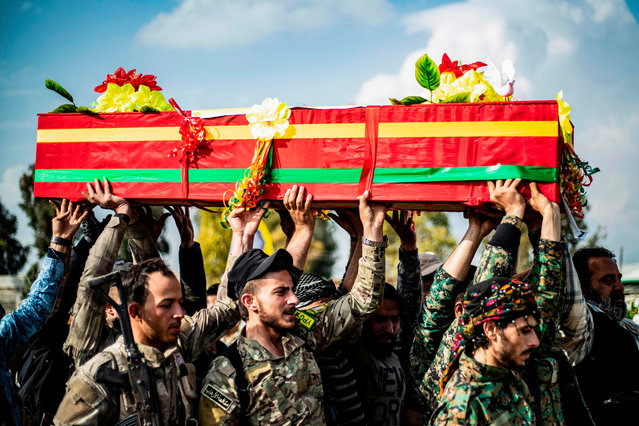 Members of the Kurdish-led Syrian Democratic Forces (SDF) carry the coffin of an Arab fighter in SDF who was killed the previous week in the eastern Deir Ezzor province, during his funeral in northeastern Syrian Kurdish-majority city of Qamishli on April 10, 2019. (Photo by Delil Souleiman/AFP Photo)