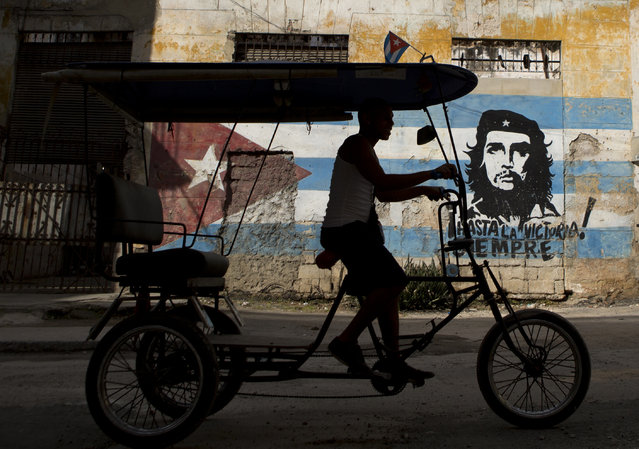 "A bicycle taxi rides past a building painted with a Cuban flag and an image of Che Guevara, along with the Spanish slogan ""Always toward victory!"" in Havana, Cuba, Saturday, March 19, 2016. U.S. President Barack Obama will visit the island on March 20. During his three-day trip, the first to the country by a sitting U.S. president in nearly 90 years, he will meet with President Raul Castro at the Palace of the Revolution and attend an exhibition baseball game. (Photo by Rebecca Blackwell/AP Photo)"