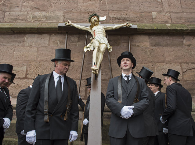 """Believers prepare the scene """"Crucifixion"""" during the Palm Sunday Procession in the old town in Heiligenstadt, Germany, Sunday, March 20, 2016. Thousands of believers from the region and all over Germany attend the procession when participants carry life-size figures showing the Passion of Christ. (Photo by Jens Meyer/AP Photo)"""