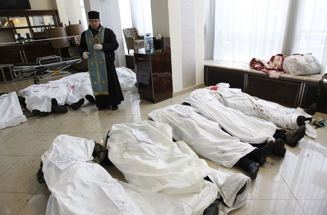 A priest stands in the lobby of the hotel Ukraine near bodies of anti-government protesters killed during clashes with riot police in Kiev February 20, 2014. (Photo by David Mdzinarishvili/Reuters)
