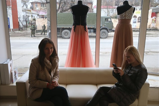 Two young women sit in a shop that sells evening gowns as heavily-armed soldiers displaying no identifying insignia stand outside in a street in the city center on March 1, 2014 in Simferopol, Ukraine. Similarly dressed soldiers stationed themselves around the Crimean Parliament building earlier in the day in what seems to be a growing military occupation of the city, which is the Crimean capital. (Photo by Sean Gallup/Getty Images)