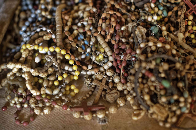 A pile of necklaces and crucifixes belonging to some of those who were slaughtered as they sought refuge inside the church sit on the altar as a memorial to the thousands who were killed during the 1994 genocide in and around the Catholic church in Nyamata, Rwanda Thursday, April 4, 2019. Rwanda will commemorate on Sunday, April 7, 2019 the 25th anniversary of when the country descended into an orgy of violence in which some 800,000 Tutsis and moderate Hutus were massacred by the majority Hutu population over a 100-day period in what was the worst genocide in recent history. (Photo by Ben Curtis/AP Photo)