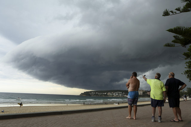 Storm clouds pass over Manly's Fairy Bower beach on Sydney's north shore as locals (L-R) Matt Fleming, Larry McMurridge and George Stantschef look on, March 5, 2014. The clouds, pushed along by a south westerly wind, generated little rain before being swept out to sea. (Photo by Will Burgess/Reuters)