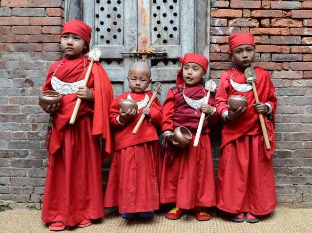 A group of Nepalese Buddhist boys pose as they attend Bratabandha, a coming-of-age ceremony in Kathmandu on March 5, 2014. In Newari culture of the Shakya caste, the heads of young boys are shaved and they wear a dress of a monk during the Bratabandha ceremony, which combines chudakarma and upanayana, among the hill communities of Nepal. (Photo by Prakash Mathema/AFP Photo)