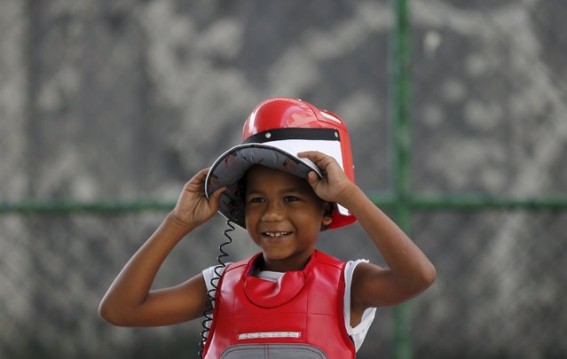 """A child from municipal school Parana smiles during the project """"Fencing School"""" in Rio de Janeiro, Brazil, March 30, 2016. (Photo by Sergio Moraes/Reuters)"""