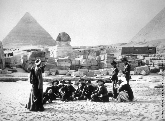 1940: Members of the New Zealand forces resting with their native guides during a visit to the Sphinx and the Pyramids at Giza