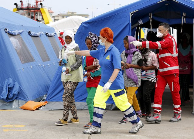 Migrants are helped after they disembarked from the Migrant Offshore Aid Station (MOAS) ship MV Phoenix in the Sicilian harbour of Messina, Italy May 16, 2015. (Photo by Antonio Parrinello/Reuters)