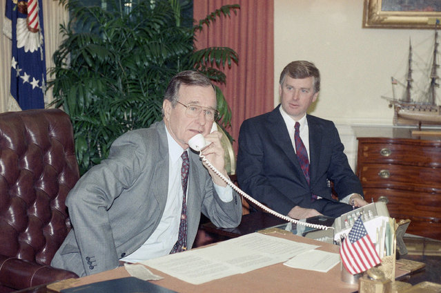 President George H. W. Bush, left, speaks to the orbiting Columbia astronauts with Vice Pres. Dan Quayle from the Oval Office, Thursday, Jan. 18, 1989, Washington, D.C. George Herbert Walker Bush was the 41st U.S. President serving form 1989 to 1993. (Photo by Ron Edmonds/AP Photo)