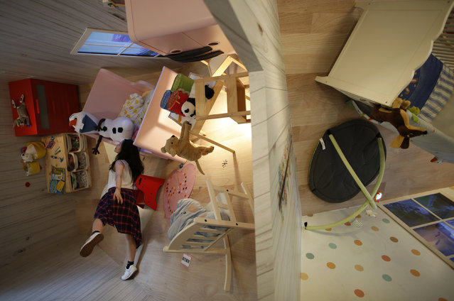 A visitor poses inside a three story upside-down family sized house at the Huashan Creative Park in Taipei, Taiwan April 7, 2016. (Photo by Tyrone Siu/Reuters)