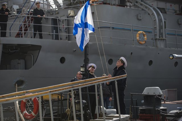 Officers of the Ukrainian navy ship Lutsk raise a Russian navy flag aboard the Lutsk, which has been seized by Russia, in Sevastopol, Thursday, March 20, 2014. Pro-Russian crowds seized two Ukrainian warships Thursday. Shots were fired but there were no casualties as the Ukrainian corvette Khmelnitsky was seized in Sevastopol. Another ship, the Lutsk, was also surrounded by pro-Russian forces. (Photo by Andrew Lubimov/AP Photo)