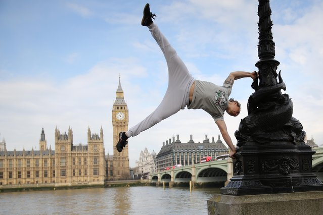 British Parkour expert Tim Shieff performs a hand-stand in front of the House of Commons, as he launches Jungle Book inspired Parkour masterclasses on London's Southbank, to celebrate the release of The Jungle Book, Thursday, April 14, 2016. (Photo by Joel Ryan/Invision/AP Photo)