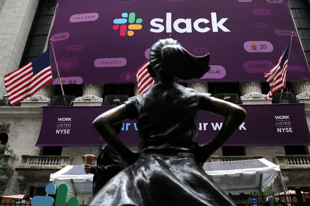 """The Slack Technologies Inc. logo is seen behind the """"Fearless Girl"""" statue outside the New York Stock Exchange (NYSE) during the company's direct listing in New York, U.S. June 20, 2019. (Photo by Brendan McDermid/Reuters)"""
