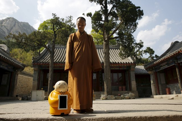 Master Xianfan looks at robot monk Xian'er as he prepares to pose for photograph in the main building of Longquan Buddhist temple on the outskirts of Beijing, April 20, 2016. (Photo by Kim Kyung-Hoon/Reuters)