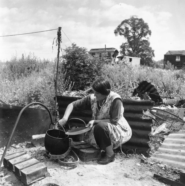 A Romany woman cooks dinner in an iron pot hung over an open fire at the Corke's Meadow encampment in Kent, 28th July 1951. (Photo by Bert Hardy/Picture Post/Getty Images)