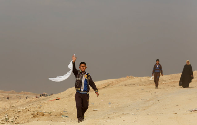 A displaced Iraqi boy waves a white flag as he flees his home while Iraqi forces battle with Islamic State militants, in western Mosul, Iraq March 8, 2017. (Photo by Suhaib Salem/Reuters)