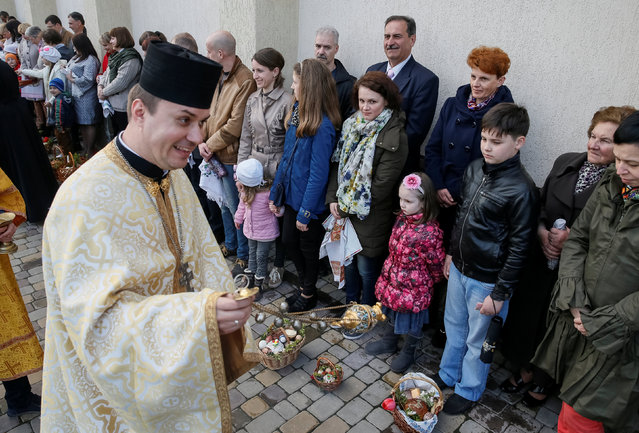 A priest greets believers before a Greek-Catholic Easter service in Pustomyty village near Lviv, Ukraine, April 30, 2016. (Photo by Gleb Garanich/Reuters)