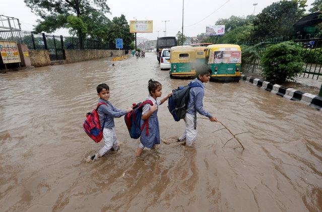 Schoolchildren wade through a flooded street after heavy rains in New Delhi, India, August 6, 2019. (Photo by Adnan Abidi/Reuters)