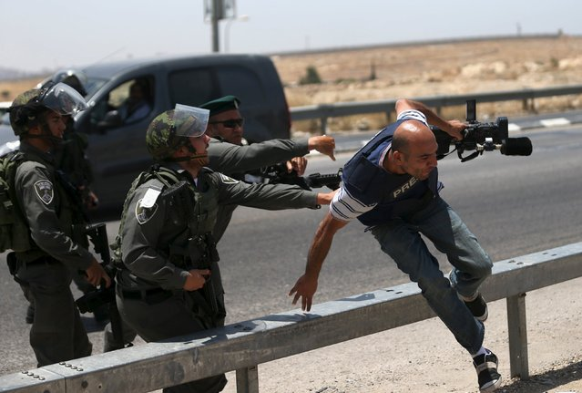 A cameraman runs away from Israeli border policemen during a protest marking the first anniversary of the killing of 16-year-old Palestinian Mohammed Abu Khudair, who was burnt in Jerusalem in a suspected revenge attack for the kidnapping and slaying of three Israeli teens last year, near the West Bank city of Ramallah July 2, 2015. Abu Khudair's abduction and killing sparked violent protests and calls from Palestinians for a new uprising against Israel last year. (Photo by Mohamad Torokman/Reuters)