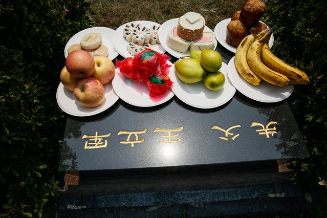 Bakery and fruits are placed on the gravesite left by Chinese people for their deceased relatives to mark the Qingming Festival at the Changqingyuan cemetery in Beijing, China, 03 April 2017. The Qingming Festival, also known as the Tomb-Sweeping Day, is marked by Chinese people by going to the cemetery to cleaning up tombs, bringing flowers, and making offerings to their ancestors. (Photo by Roman Pilipey/EPA)
