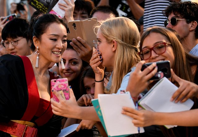 """Actor Li Gong looks at a fan's phone on the red carpet ahead of the """"Lan Xin Da Ju Yuan"""" (Saturday Fiction) screening during the 76th Venice Film Festival at Sala Grande on September 04, 2019 in Venice, Italy. (Photo by Piroschka van de Wouw/Reuters)"""