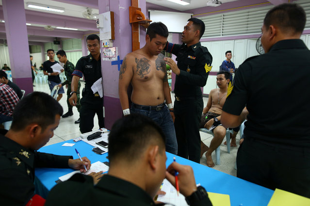 A man is examined during an army draft held at a school in Klong Toey, the dockside slum area in Bangkok, Thailand, April 6, 2017. (Photo by Athit Perawongmetha/Reuters)