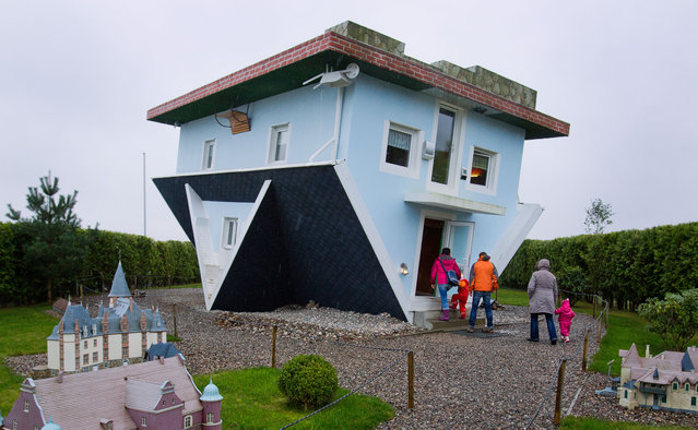 Visitors enter a house standing upside down in Trassenheide on the Baltic Sea island of Usedom, northeastern Germany, on November 2, 2013. The house was already constructed in the year 2008 by two Polish initiators, who also designed the house's interior upside down. (Photo by Jens Buettner/AFP Photo/DPA)