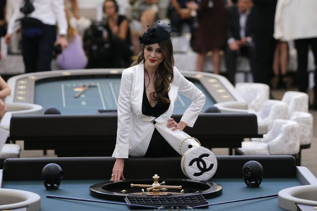 A guest poses before the Haute Couture Fall Winter 2015/2016 fashion show by German designer Karl Lagerfeld for French fashion house Chanel at the Grand Palais which is transformed into a casino in Paris, France, July 7, 2015. (Photo by Stephane Mahe/Reuters)
