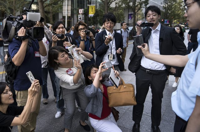 A customer holding an iPhone 11 box is surrounded by the media outside the Apple Marunouchi store on September 20, 2019 in Tokyo, Japan. Apple Inc. launched the latest iPhone 11 models featuring a dual-camera system today. (Photo by Tomohiro Ohsumi/Getty Images)