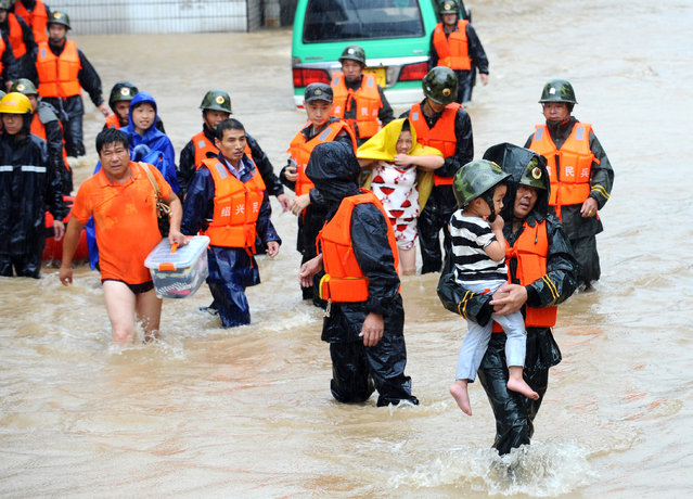 Militia members evacuate residents from a neighborhood flooded by heavy rains from Typhoon Chan-Hom in Shaoxing in eastern China's Zhejiang province Saturday, July 11, 2015. (Photo by Chinatopix via AP Photo)