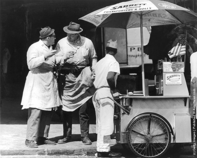 1965:  Two butchers stop to chat after buying hot dogs from a street vendor in the Times Square area of New York