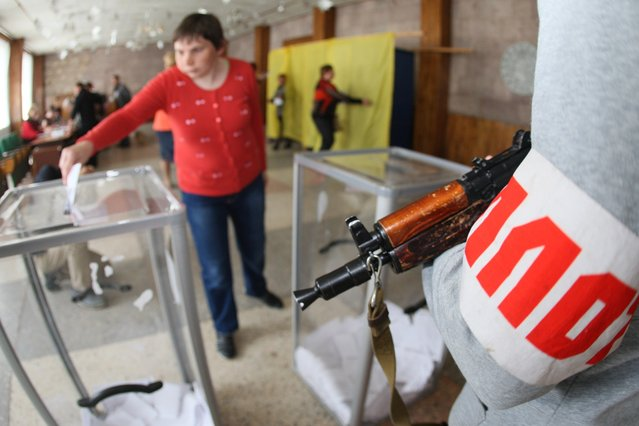 "An armed  pro-Russian activists stands guard as a woman casts her ballot for the referendum called by pro-Russian rebels to split from the rest of Ukraine, on May 11, 2014 in Donetsk. The vote, carried out as two ""referendums"" in provinces where the insurgents hold more than a dozen towns, marks a serious deepening of the political crisis in Ukraine, which has pushed East-West relations to lows not seen since the end of the Cold War. (Photo by Alexander Khudoteply/AFP Photo)"