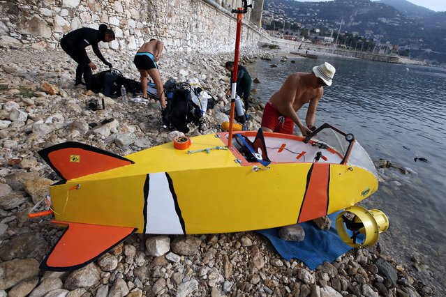 """French adventurer and researcher Stephane Rousson (R) and his team get ready for the first test of """"Nemo"""", a three-metre long submarine with electric propulsion, on July 15, 2015 in Villefranche-sur-Mer, southeastern France. (Photo by Valery Hache/AFP Photo)"""