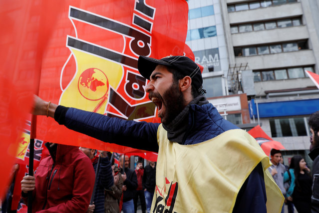 A man shouts slogans while protesters hold banners as they attempt to defy a ban and march on Taksim Square to celebrate May Day in Istanbul, Turkey. (Photo by Umit Bektas/Reuters)
