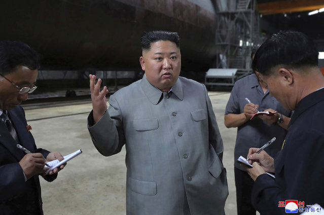 """In this undated file photo provided on Tuesday, July 23, 2019, by the North Korean government, North Korean leader Kim Jong Un, center, speaks while inspecting a newly built submarine to be deployed soon, at an unknown location in North Korea. North Korea fired two unidentified projectiles into the sea on Thursday, July 25, South Korea's military said, the first launches in more than two months as North Korean and U.S. officials work to restart nuclear diplomacy. Independent journalists were not given access to cover the event depicted in this image distributed by the North Korean government. The content of this image is as provided and cannot be independently verified. Korean language watermark on image as provided by source reads: """"KCNA"""" which is the abbreviation for Korean Central News Agency. (Photo by Korean Central News Agency/Korea News Service via AP Photo/File)"""